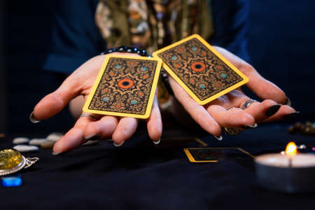 Cartomancy. The fortune teller holds out two Tarot cards on her palms. Close up. The concept of divination, astrology and esotericism.