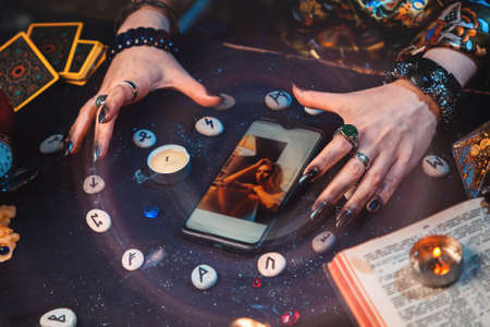 The fortune teller casts a spell on a smartphone with photo. Hands and device close-up. The view from the top. Magic aura. The concept of modern online divination and witchcraft.