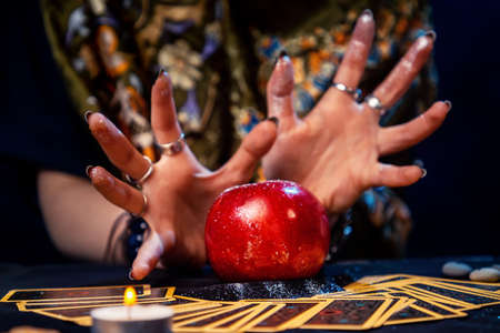 A fortune teller conjures a red apple lying on the Tarot cards. Close up. The concept of divination, astrology and esotericism.