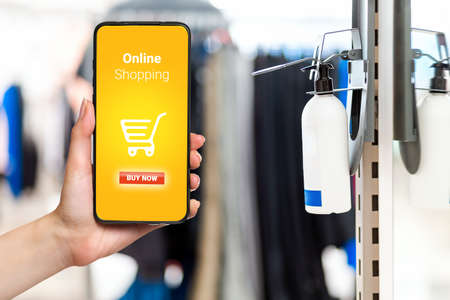 A bottle of hand sanitizer is fixed at the entrance to the store. Hand with smartphone on the left side. Concept of preventive measures during a viral pandemic.