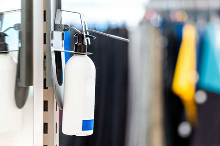 A bottle of hand sanitizer fixed at the entrance to the store. Close-up. Blurred background. Copy space. Concept of hygiene products in public places and shops.