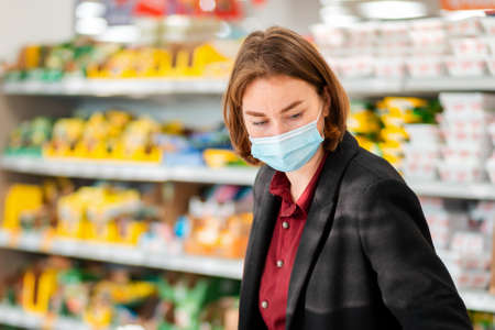 Shopping. Portrait of a young woman in a medical mask choosing products in a supermarket. The concept of shopping and the new normal.