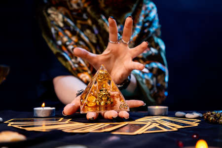 The fortune teller holds a glass pyramid with gold in her hands and casts a spell over it. There are Tarot cards on the table. Close-up. The concept of divination, magic and esotericism.