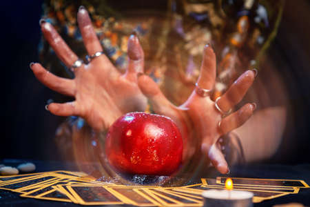 A fortune teller conjures a red apple lying on the Tarot cards. A magical aura emanates from the fruit. Close up. The concept of divination, astrology and esotericism.
