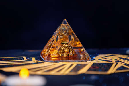 A glass pyramid with a Golden frog. Tarot cards are scattered on the table. Close-up. Copy space. The concept of divination, magic and esotericism.