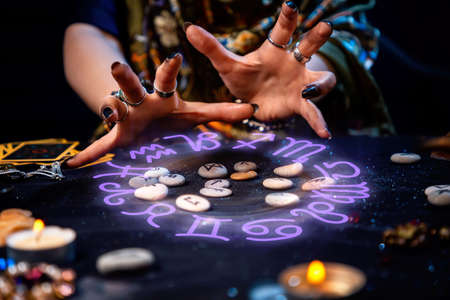 The female hands of the soothsayer read the runes. The zodiac circle glows above the runes. The concept of divination, astrology and predicting the future.