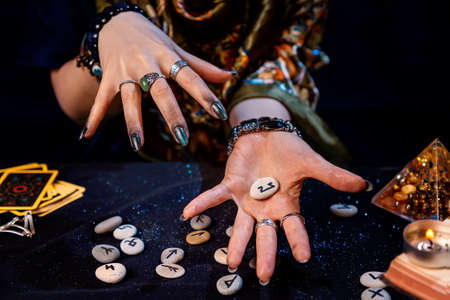 The fortune teller holds a rune in the palm of her hand. Top view. The concept of divination, astrology and predicting the future. Stock fotó