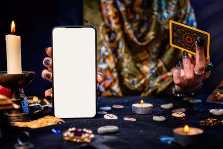 The fortune teller is holding a Tarot card and a smartphone with a white screen. Mock up. Close-up. The concept of divination, magic and esotericism.