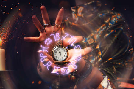 The fortune teller holds a watch on a chain in her hands and conjures over it. A luminous zodiac circle is depicted around the clock. The concept of divination, astrology and predicting the future.