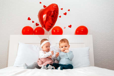 Cute boy and girl sitting together on a white bed. Red balloons hang over the bed. The Concept Of Valentine's Day.