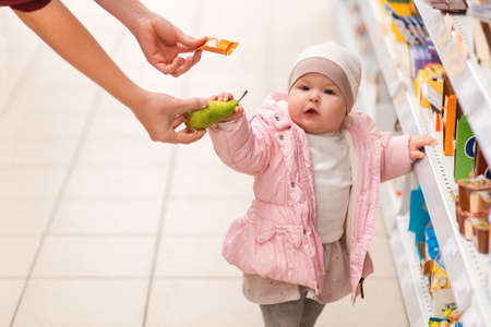 Shopping. Portrait of cute child is standing near the shelf with products, and will choose between a candy and a pear, which mom offers. The concept of shopping and consumerism.