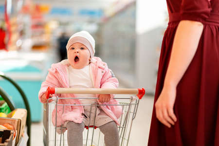 Shopping. A funny yawning child is sitting in a shopping cart at supermarket. The concept of family shopping and parenting.