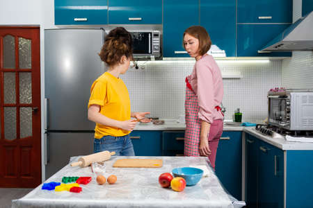 Two young Caucasian women cook together in the kitchen. The concept of LGBT couples and family cooking.