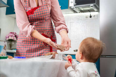 A mother in an apron shows a small child a cookie. The concept of home cooking and cooking together with children. Stock fotó