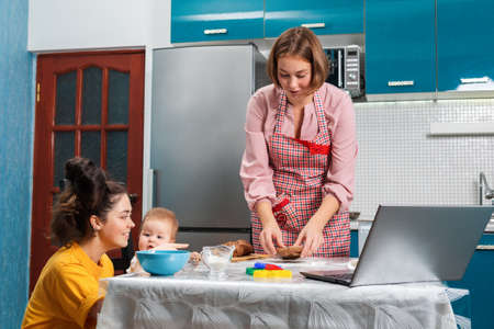 A young woman in an apron makes cookies. There is a laptop on the table. A baby is sitting on a chair next to me, in the arms of a young woman. The concept of home cooking and modern technologies.