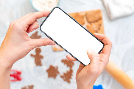 Female's hands takes a photo of ginger cookies on a smartphone. Flat lay. Mock up. The background is blurred. The concept of Christmas and modern technologies.