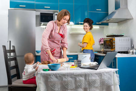 Two young women and a baby are preparing gingerbread at home. The laptop is on the table. The concept of home cooking, online communication and LGBT couples.