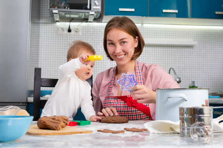 Portrait of a young happy mother makes cookies with her baby and shows a cookie cutter. Kitchen in the background. The concept of home-made food and cooking with children. Stock fotó