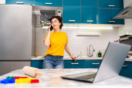 A young beautiful woman communicates on a smartphone in the home kitchen. In the foreground, a blurry view shows a laptop on a table. The concept of communication and of cooking at home. Stock fotó