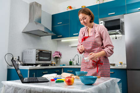 A woman cooks in the kitchen using online recipes on her laptop. Indoor. The concept of cooking at home using online recipes.