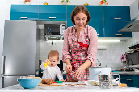 Portraits of smiling mother and baby make gingerbread together. Mother's Day concept and cooking festive home-cooked meals with children. Stock fotó