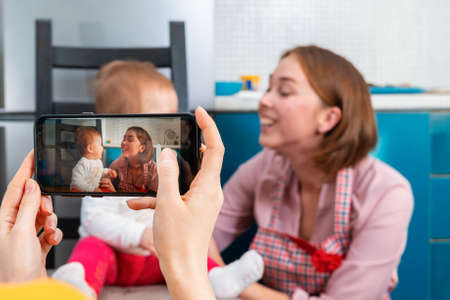 Female's hands shoot a portrait of a mother and child on a smartphone. Family in the background in a blur. The concept of modern technologies in everyday life.