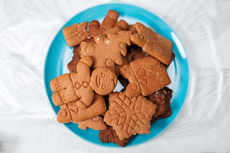 Christmas decorations. Gingerbread lying on a plate. Flat lay. Close up. Holiday food.
