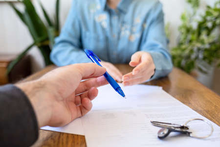 An employee gives the client a pen to fill out documents. Hands close-up. There are papers and keys on the table. Rental and purchase of real estate.