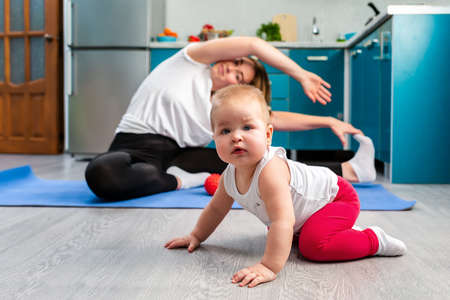 The child crawls on the floor. In the background, in a blur, a young mother is stretched out on a rug in the kitchen. Concept of home sports training with children. Stock fotó