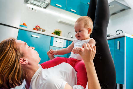 A mother with her baby doing fitness in the kitchen. Bottom view. The concept of home sports training with children.