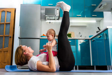 A mother with her baby is having fun doing fitness on the mat in the kitchen, lifting her legs. The concept of home sports training with children. Stock fotó