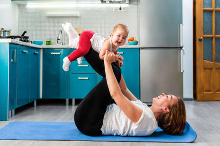 A smiling mother holds a cute happy baby in her arms while having fun doing fitness together on a mat. The concept of home sports training with children.