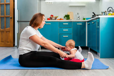 A young mother with her baby is doing yoga on a mat in the kitchen. The concept of home sports training with children.