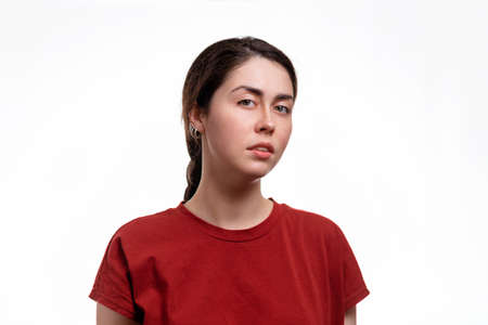 Portrait of a young woman with a disgruntled face. White background. the concept of human emotions.