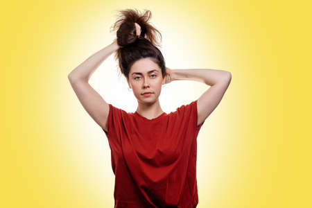 A young woman holds her hair in a knot with her hands. Yellow background. Copy space. Hair care concept.