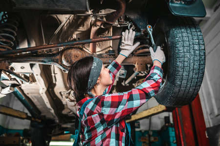 Portrait of a young female mechanic in uniform and gloves who repairs a car. The car is on the lift. Bottom view. Stock fotó