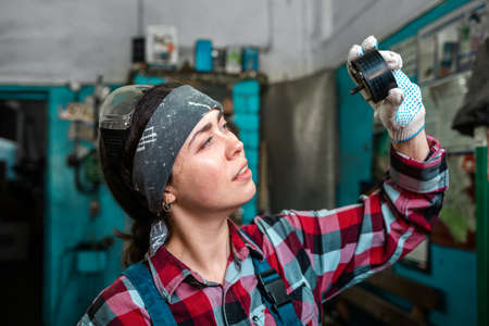 Portrait of a young female mechanic in uniform, wearing gloves and safety glasses on her head, checking a car part. Indoor. Close up. Stock fotó