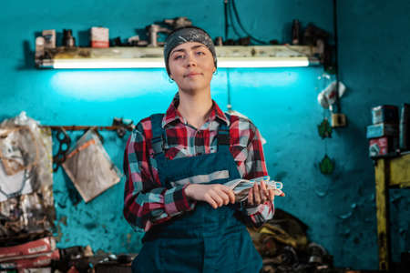 Portrait of a young smiling female mechanic in uniform, posing with gloves in her hands. Working room in the background. The concept of gender equality.