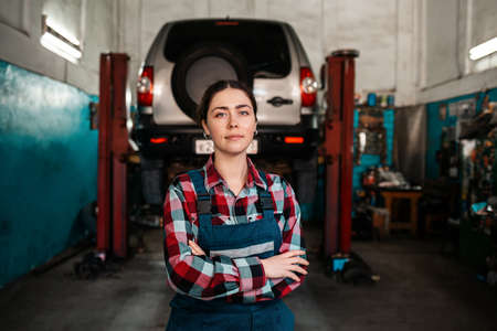 Portrait of a young female mechanic in uniform, posing with her arms crossed. In the background there is an auto repair shop and a car on a lift.