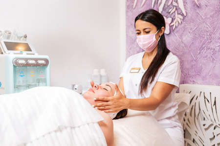 Cosmetology. A professional cosmetologist in a medical mask makes a massage procedure for the client. Concept of precautionary measures during a pandemic.