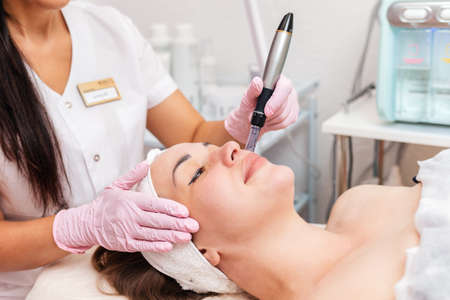 Beauty salon. Smiling cosmetologist in rubber gloves makes fractional mesotherapy of the face to the client. Close up of face. Concept of professional modern cosmetology and treatment.