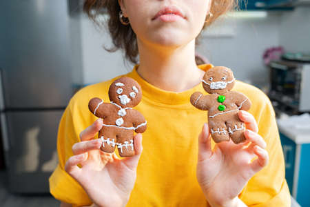 A caucasian woman shows two gingerbread men with icing in the form of a medical mask and a screaming face. Close-up. The concept of Christmas holidays during the coronavirus.