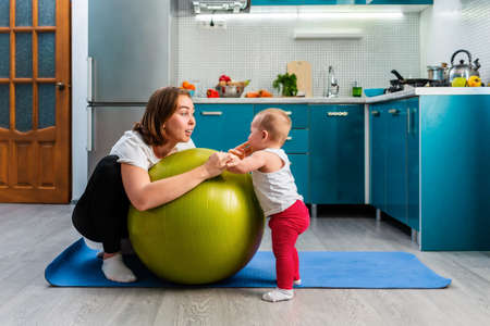Yoga at home. A smiling young mother leaning on a fit ball and talking with her baby. The concept of fitness with children at home.