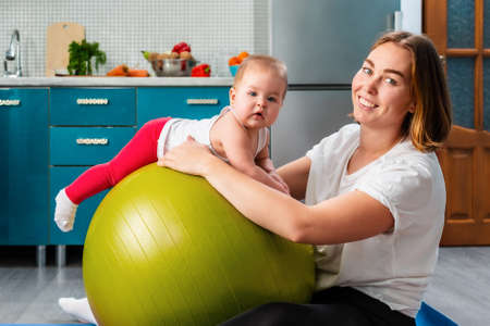 Yoga at home. Portrait of a young mother leaning on a fit ball and posing with your baby. The concept of fitness with children at home. Stock fotó