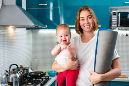 Home yoga. A young smiling mother holds her baby in her arms, and a sports mat rolled up. In the background is the kitchen. The concept of sports activity at home. Stock fotó