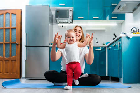 Sports training at home. A young mother sitting on a sports mat, teaching the baby to walk. The concept of yoga and baby's education. Stock fotó