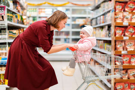 Portrait of a young mother smiling rolls a grocery cart around the store, in which the baby is sitting. Side view. The concept of family shopping. Stock fotó