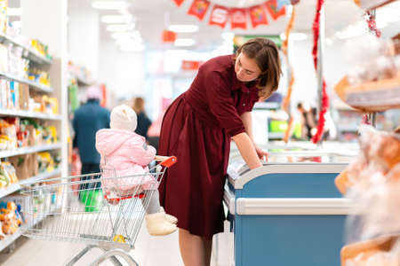 A young mother takes out food from the refrigerator in the supermarket. Her child is sitting next to her in a grocery cart. The concept of shopping.