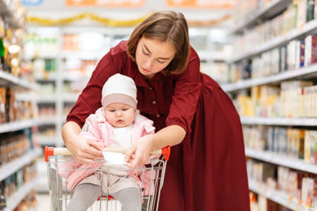Portrait of young mother reads a shopping list, showing it to her baby. The concept of family shopping.