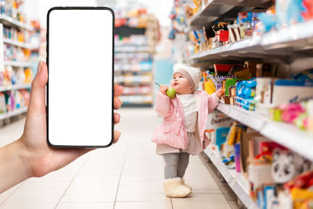 Shopping. A small child stands at the supermarket shelves with a pear in his hand. The hand on the left side holds the smartphone. The concept of online shopping and consumerism.